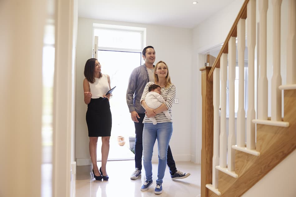 picture of Realtor Showing Young Family Around Property For Sale