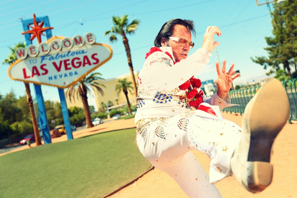 picture of Elvis look-alike impersonator man in front of Welcome to Fabulous Las Vegas sign on the strip. People having fun and Viva Las Vegas concept image with Elvis impersonator doing some crazy moves.