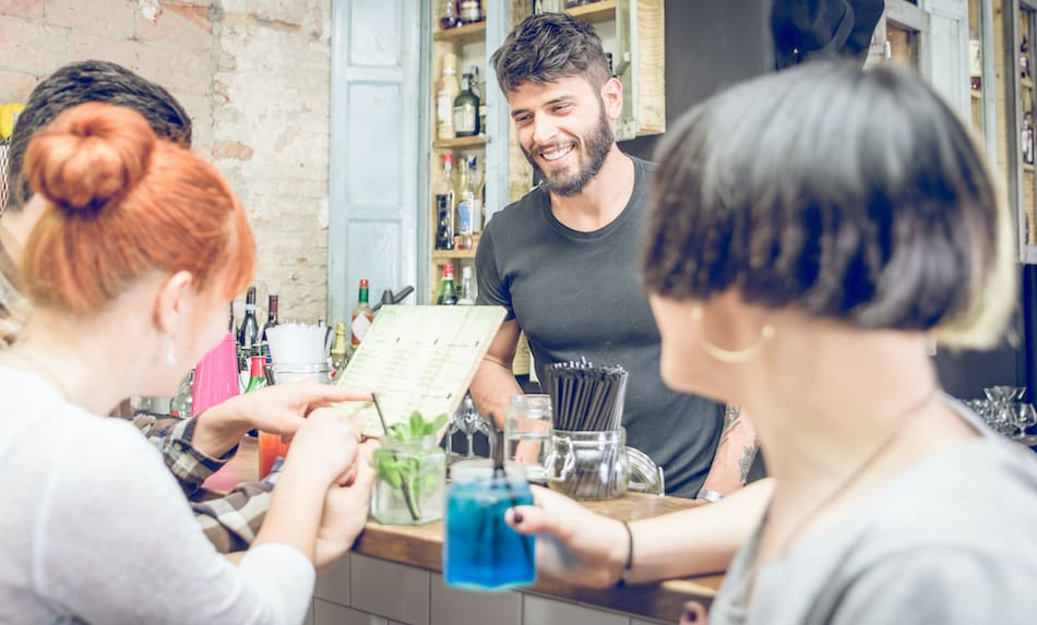 picture of group of friends choosing cocktail from the menu in a bar . concept about beverages, and people