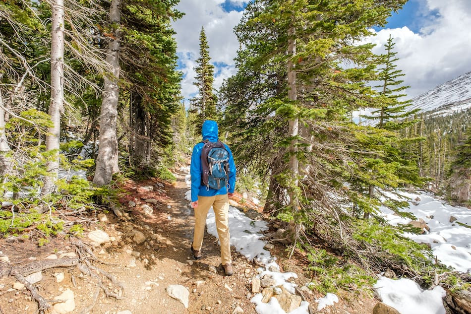 picture of Tourist with backpack hiking on snowy trail in Rocky Mountain National Park, Colorado, USA.