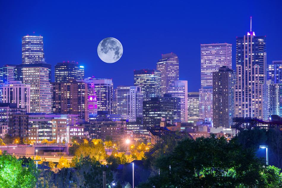 picture of Denver Colorado at Night. Denver Downtown Skyline and the Full Moon on Clear Sky.