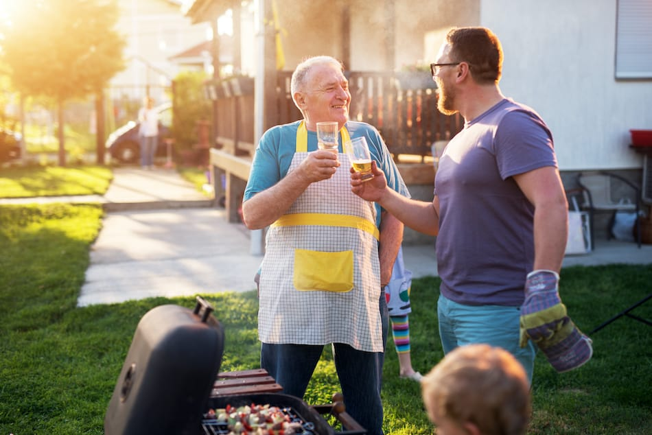 picture of Elderly Father and mature son are saluting with the beer in front of the grill in their Rhode Island house backyard on a beautiful day.