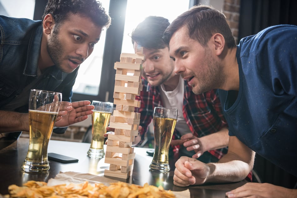 picture of a diverse group of friends playing jenga game in an austin texas bar