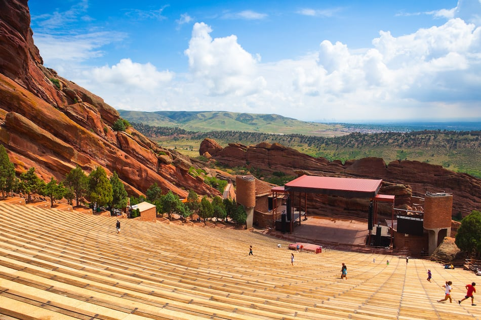 Denver, Famous Red Rocks Amphitheater in Morrison. Red Rocks Amphitheatre is a rock structure near Morrison, Colorado, 10 miles west of Denver, where concerts are given in the open-air amphitheatre.
